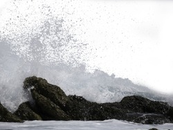The sea wave crashing on the rock and make the splashing water and white air foam bubble. Isolated on white background with clipping path.