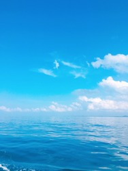 the sea with blue sky and white clouds.