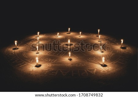 The Seal of the Seven Archangels. Illuminated with candles. Dark background. Side view. Scary, mystical occultism. ストックフォト ©