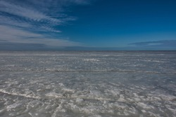 The seascape of the spring Baltic Sea, covered with the last grayish soft and watery ice, under a blue sky with slight clouds on a sunny day.