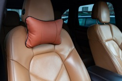 The seats in the car are made of brown leather with pillows for the neck and rest during long trips and travels.