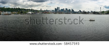 The Seattle skyline white white clouds and shoreline of Lake Union