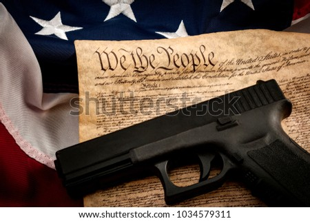 The second amendment and gun control in america concept with a handgun and the american constitution on the USA flag with close up on the