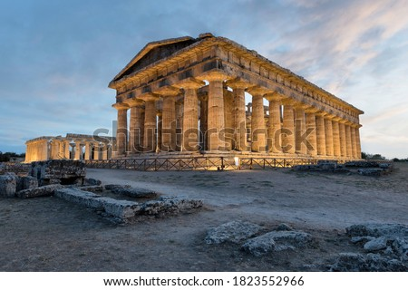 The Second Temple of Hera in Paestum, Southern Italy. The magnificent beauty of history framed with the technology of modern times. Isolated temple with a dramatic orange sky at sunset in the back