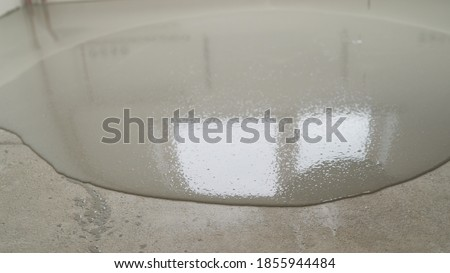 The self-leveling floor is poured onto the floor. The worker pours the solution from the self-leveling floor. Self-leveling floor laying. hand spreading poured concrete and leveling concrete with Foto stock ©