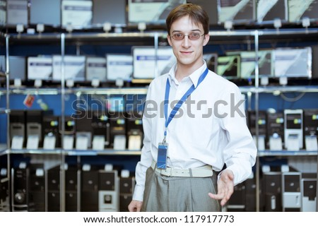 The seller-adviser on a background of computer monitors