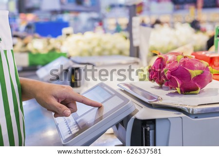 The seller is weighing fruit and points the fingers on the screen electronic scales in supermarket.