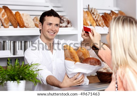 The seller sells to the girl bread in a bakery