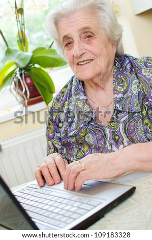The senior hand presses the laptop keyboard button