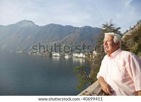 The senior man enjoy his travel by the lake of Switzerland.
