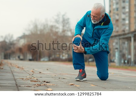 The senior man use hands hold on his knee while running outdoor