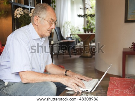 The senior man uses his laptop in the living room.
