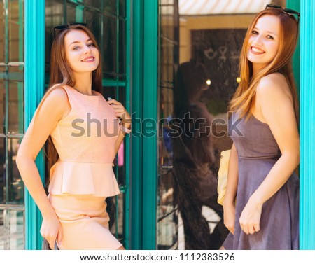 the sensual poses of the girls leaned to the glass wall and posed to the photographer and between them the glass doors #1112383526