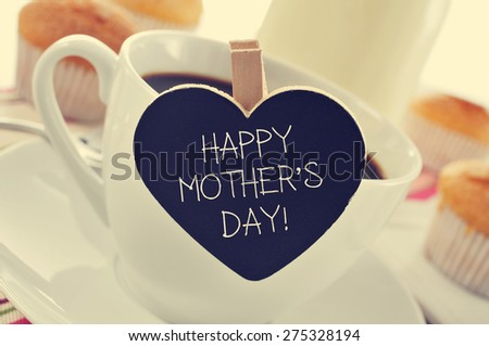 the sentence happy mothers day written in a heart-shaped blackboard placed in a cup of coffee, with some muffins in the background in a set table for breakfast #275328194