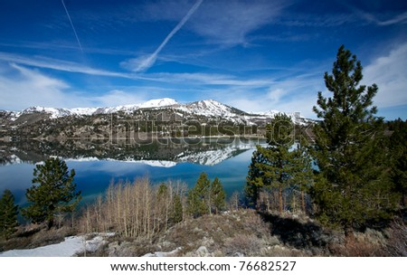The serene reflection of June Lake stretching across a beautiful panorama. - stock photo