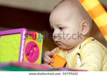 The serious baby playing with block toy at home