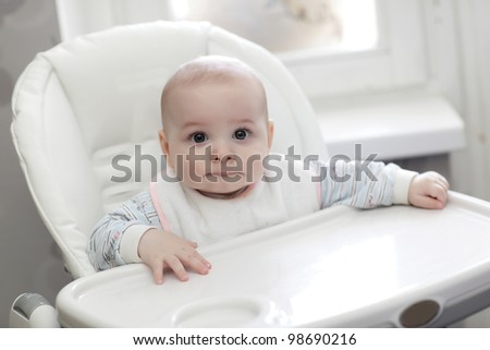 The serious baby sitting in highchair at home