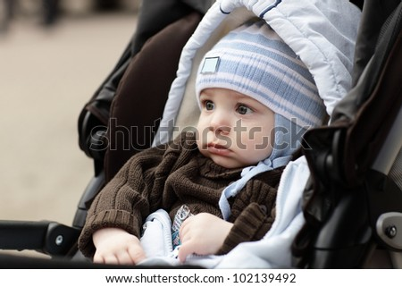 The serious child is sitting in stroller
