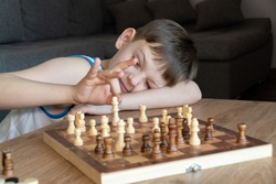The serious child lost in thought playing chess. Playing board games, on coronavirus quarantine. The child playing chess.