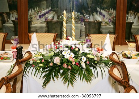 The served celebratory wedding table decorated with flowers and candles