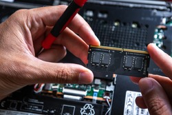 The service technician holds a new RAM in his hands, which he wants to put in the laptop, and he hopes that after that it will work.
