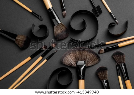 The set of brushes for applying make-up of different usage: for lips, eyes, lashes, skin, brows. Professional equipment of make-up artist. Spiral curls of black carton create artistic atmosphere.
