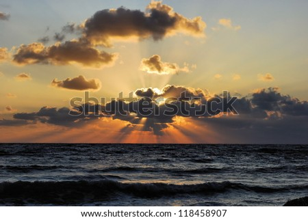 The setting sun behind the clouds over the Mediterranean Sea waves