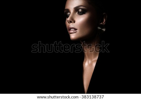 the sexy strict woman with makeup and a fashionable  hairstyle poses in studio on black background