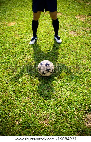 The shadow of a asian football player together with a football on green grass