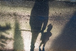 The shadow of a child and his father on the road of tiles. Dark silhouette. The father leads the baby by the hand.