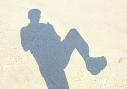 The shadow of a man raising his legs on the cement floor