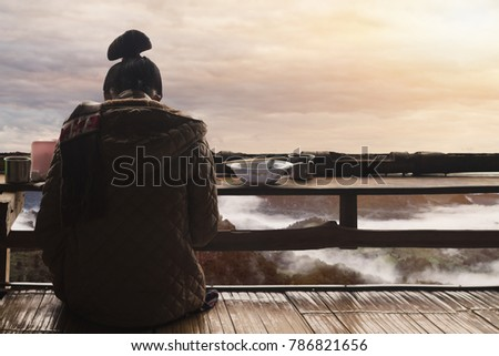 The shadow of a woman sitting on her back on the balcony alone to wait for her lover back. Sky background in the bright morning of winter at sunrise on the horizon above the mountain.