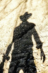 the shadow of the male cowboy on a sunset evening in the country