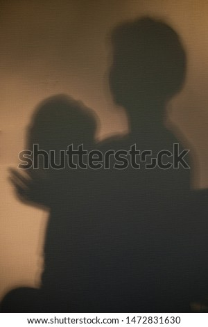 The shadow on the wall from a woman who holds a small child in her arms. The child threw back his head, a woman holds the baby's head with her hand. No focus. Soft focus. Abstract #1472831630