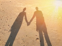 The shake hand's shadow of love couple on the shore with the sunlight.