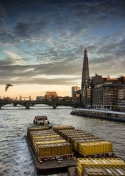 the shard during sunsets, view from milllennium bridge with tug boat and barge passing by