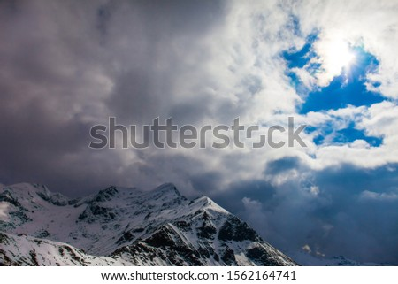 The sharp peaks of the Austrian Alps are covered with the first snow. Powerful clouds cover the sky. Grossglockner sightseeing road. The roadside is fenced. Ecological and photo tourism concept