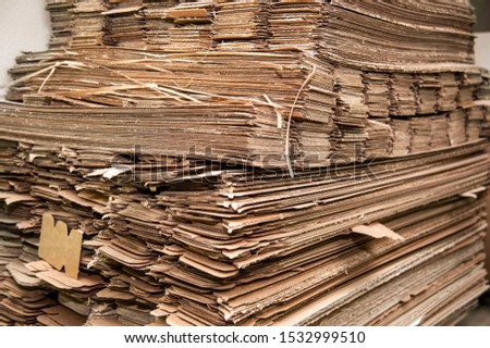 The sheets of brown corrugated cardboard are on top of one another, among them are good and discarded sheets, discarded cardboard boxes that will be recycled
