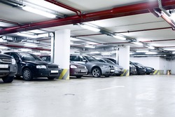 The shined underground garage with the moving cars and parked cars