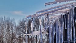 The shiny dangerous icicles hanging from the roof of a building against the sky