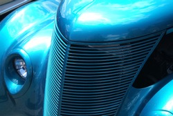 The shiny front  grill of this hotrod is blue chrome.