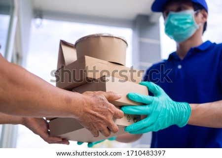 The shipper wears a mask and gloves, delivery food to the home of the online buyer. stay at home reduce the spread of the covid-19 virus. The sender has a service to deliver products or food quickly Stockfoto ©