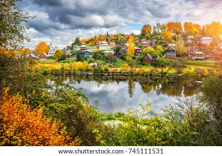 The Shokhonka River in Plyos in the autumn decoration and many small houses in the town