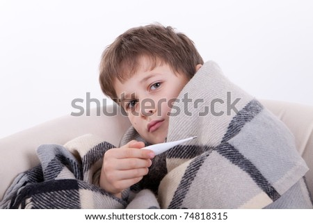 The sick boy covered by a checkered plaid, holds a thermometer in a hand - stock photo