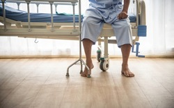 The sick  or elderly Asian old man couldn't walk sitting alone on the patient's bed with walking stick waiting for the doctor and nurse for treatment or cure in the hospital or healthcare