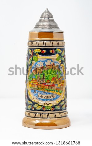 the side of a beer stein with a painting of Salzburg, Austria