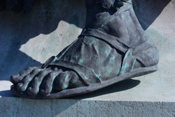 The side view close up detail of ancient man statue on a pedestal with feet toes wearing sandals in Budapest, Hungary