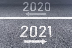 The sign arrow back to the 2020 year and go ahead 2021 Written on The asphalt road background The vision new year of 2021.