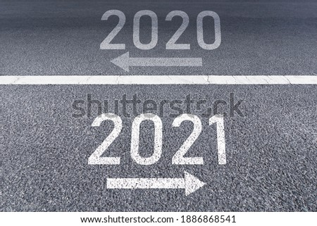 Photo of  The sign arrow back to the 2020 year and go ahead 2021 Written on The asphalt road background The vision new year of 2021.