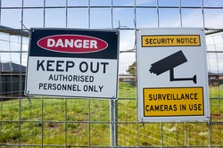 The sign of 'Danger Keep Out Authorised Personnel Only' and ' Security notice Surveillance cameras in use' on a metal construction barrier by a lot of private vacant land. Concept of no trespassing.